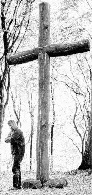 49_Das Kreuz mit dem Kreuz_© Martin Hopfengart. Das Bild zeigt einen Mann, der unter einem mehrere Meter hohen Kreuz steht und sich von diesem abwendet.