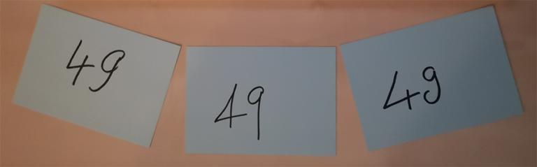 """Drei umgedrehte Zettel auf einem Tisch. Auf jedem Zettel die Aufschrift """"49"""""""